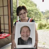 Mieko Okubo holds a photograph of her father-in-law, Fumio Okubo, who committed suicide at the age of 102 in April 2011, about a month after the Fukushima nuclear crisis started. They both lived in the village of Iitate, Fukushima Prefecture. | KYODO