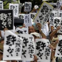 Protesters holding placards shout slogans during a rally against Prime Minister Shinzo Abe's administration and the ruling coalition's security legislation outside the Diet building in Tokyo on Saturday. The placards read in Japanese, 'Abe's politics are unforgivable.' | REUTERS