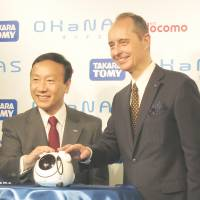 NTT Docomo President Kaoru Kato (left) and Tomy Co. President Harold Meij show off Ohanas, a communication robot that uses Docomo's cloud-based voice agent technology, in Tokyo on June 4. | KAZUAKI NAGATA