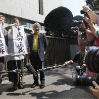 Lawyers hold up signs saying 'mandatory prosecution' and 'citizens' justice' in front of the Tokyo District Court on Friday after an independent judicial panel of citizens decided that three former executives of Tokyo Electric Power Co. merit indictment. | KYODO