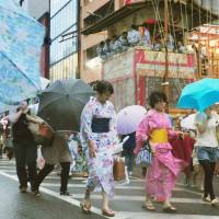Visitors to the Gion festival in Kyoto are hit by strong wind and rain Thursday as a typhoon approaches. Festival organizers announced Friday morning that they will hold the procession of Yamahoko floats Friday as scheduled. | KYODO