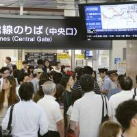 Passengers check a monitor for train delay information at JR Osaka Station on Saturday after heavy rainfall caused by a typhoon wreaked havoc in the area. | KYODO