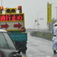 A worker guides cars Thursday away from taking Route 55 in Muroto, Kochi Prefecture, which was closed due to a typhoon. | KYODO