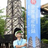 A tour guide raises a flag Monday to celebrate that an industrial facility in Izunokuni, Shizuoka Prefecture, has been granted World Cultural Heritage status. | KYODO
