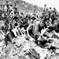 Okinawa residents, many of them wounded, surrender in June 1945 in this image taken by the U.S. military. | COURTESY OF OKINAWA PREFECTURAL ARCHIVES / KYODO