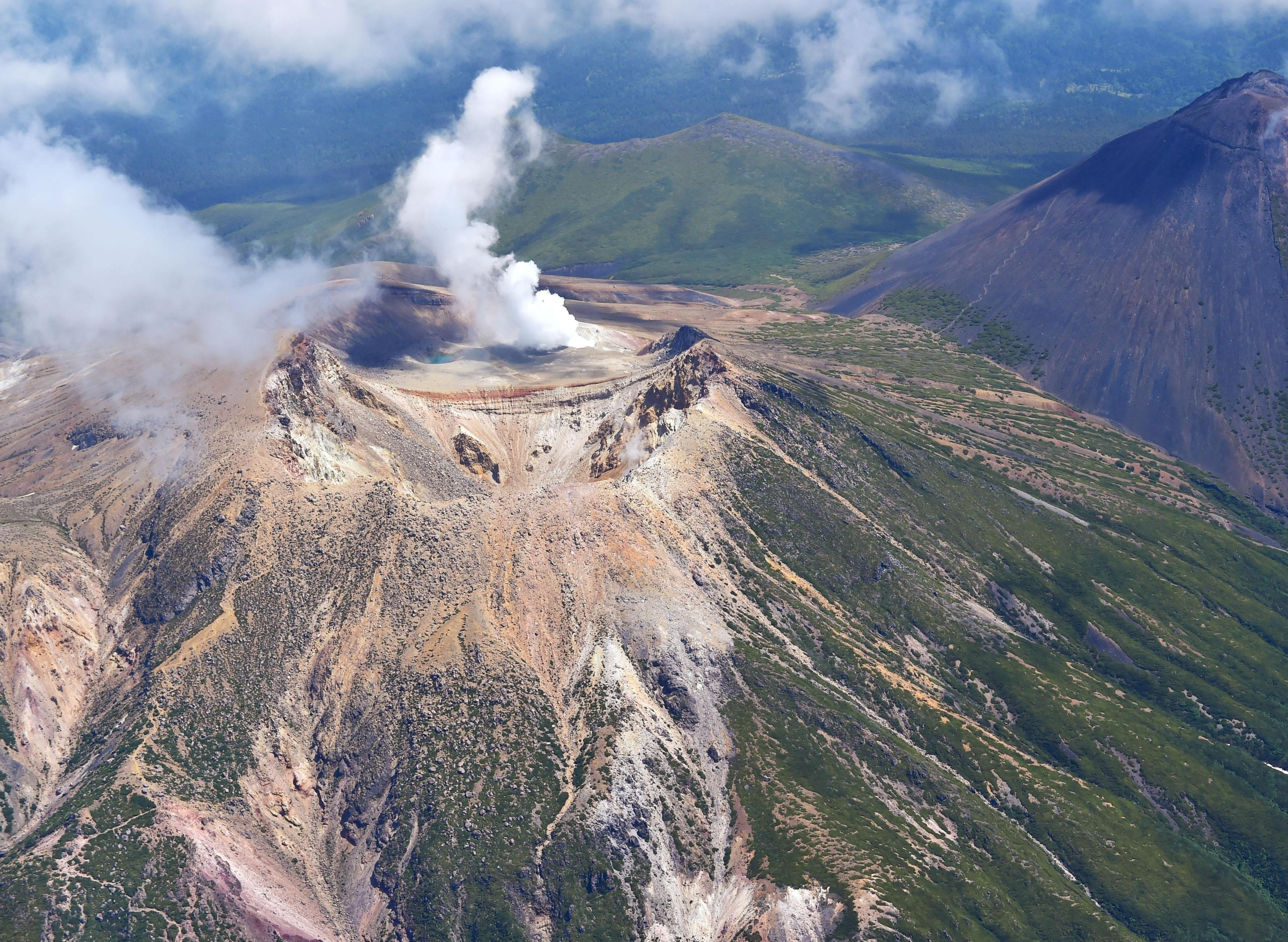Smoke spews from the top of Mount Meakandake in eastern Hokkaido on June 29. The volcanic threat level was raised Tuesday out of fear of a small eruption. | KYODO
