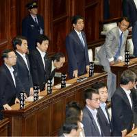 Prime Minister Shinzo Abe stands with other lawmakers Tuesday in the Lower House after the chamber passed a bill to redraw electoral districts. | KYODO