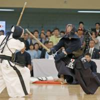 Get the blood pumping: Masahiro Shodai lunges toward his opponent at this year's Kendo World Championships held in May at Tokyo's Nippon Budokan. | KYODO