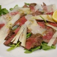 Osteria Beverino's tagliata of Kagoshima Prefecture beef is sliced thin, covered with Parmesan cheese and served on a bed of arugula. | OSTERIA BEVERINO