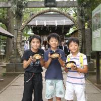 Circle of life: Three boys display their bowls of nagoshi gohan in front of a Tokyo Shinto shrine's ring of woven reeds. | © RICE STABLE SUPPLY SUPPORT ORGANIZATION
