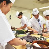 On a roll: Women make sushi rolls at Tokyo Sushi Academy in July 2013.  | KYODO