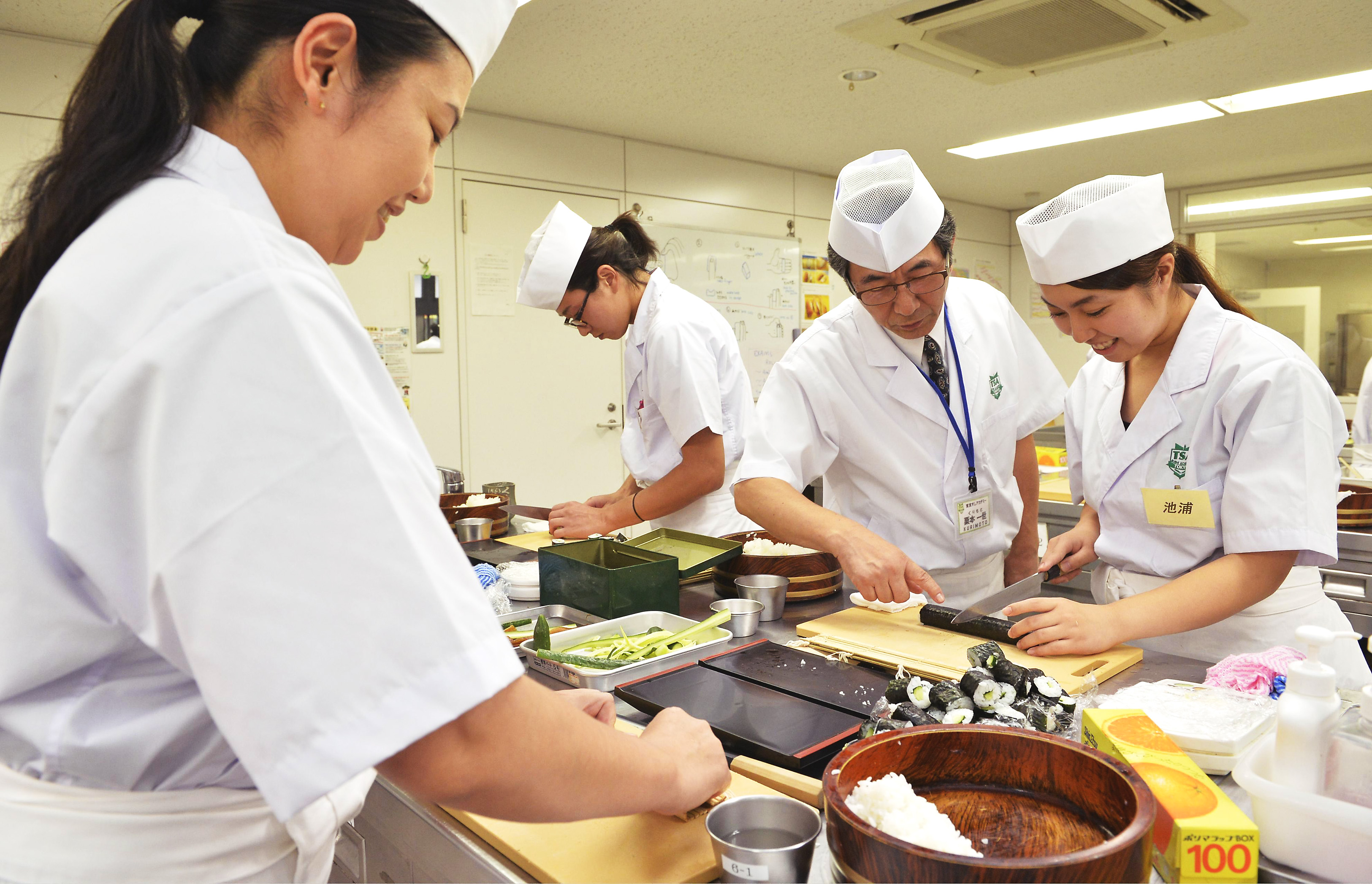 On a roll: Women make sushi rolls at Tokyo Sushi Academy in July 2013.    KYODO
