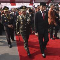 Delicate relationships: Indonesian President Joko Widodo (right) walks with military chief Gen. Moeldoko (center) and National Police chief Gen. Badrodin Haiti (left) leave an event marking the anniversary of the National Police force in Depok, near Jakarta last week. | REUTERS