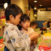 Sweet times: Children look through the goods at an old-style candy stall inside Oedo Onsen Monogatari's communal area.   OEDO ONSEN MONOGATARI