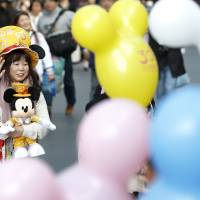 House of the mouse: A fan walks through Tokyo Disneyland, which, along with Tokyo Disney Sea, drew 31.3 million visitors in 2014, wiping the floor with its nearest domestic rival, Universal Studios Japan in Osaka.   BLOOMBERG
