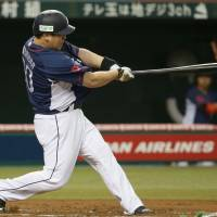 Lions slugger Takeya Nakamura bashes a three-run home run in the first inning against the visiting Marines on Saturday at Seibu Prince Dome. Seibu defeated Chiba Lotte 8-2. | KYODO