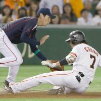 The Giants' Hisayoshi Chono slides into third base for a bases-clearing triple against the Swallows on Tuesday at Tokyo Dome. Yomiuri defeated Tokyo Yakult 5-4. | KYODO