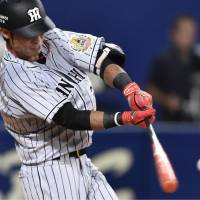 The Tigers' Taiga Egoshi hits a solo home run off the Dragons' Shinji Tajima in the seventh inning on Wednesday at Nagoya Dome. Hanshin defeated Chunichi 3-2. | KYODO