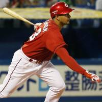 Hiroshima's Jesus Guzman hits his first home run in Japanese baseball during the fourth inning of the Carp's 5-4 win over the Swallows on Thursday. | KYODO