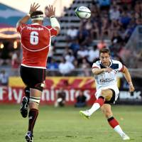 Japan's Justin Ives (left) tries to block a kick from Chris Wiles of the United States during their game last Friday. | AFP-JIJI