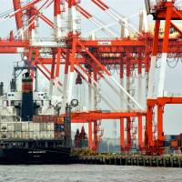 A container ship is loaded at the Port of Yokohama in 2005. | C. PERTWEE / BLOOMBERG