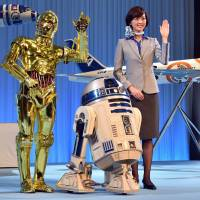 Star Wars droids C-3PO and R2-D2 pose with All Nippon Airways flight attendants as they unveil scale models of ANA Boeing 787-9 and 777-300ER aircraft in the livery of Star Wars droid characters at a news conference in Tokyo on Tuesday. ANA's R2-D2 jetliner will be launched for overseas air routes in October while the BB-8 jet plane will be launched for the North American air route next year.       AFP-JIJI