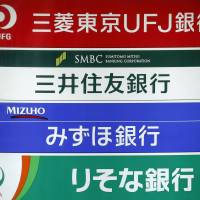 Signs for (from top) Bank of Tokyo Mitsubishi UFJ, Sumitomo Mitsui Banking Corp., Mizuho Bank Ltd., and Resona Bank Ltd. are displayed on a board in Tokyo in May.   BLOOMBERG