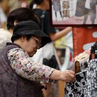 Customers look at clothes on sale at a Fukuoka shopping arcade in July. The Bank of Japan refrained Friday from expanding monetary stimulus after the central bank's governor voiced optimism the economy will pick up. | BLOOMBERG