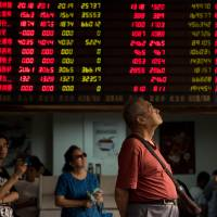 Investors monitor stock market movements at a brokerage house in Shanghai last week. Bank of Japan policymakers are increasingly worried about the impact of the Chinese yuan's moves on the Japanese economy. | AFP-JIJI
