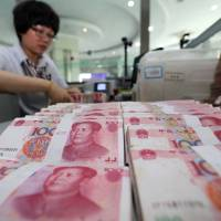 A teller counts yuan banknotes in a bank in Lianyungang, east China's Jiangsu province, on Tuesday. China's central bank Tuesday devalued its yuan currency by nearly 2 percent against the  dollar, as authorities seek to push market reforms and bolster the world's second-largest economy. | AFP-JIJI