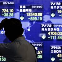 A man looks at market indices on a stock board outside a brokerage in Tokyo on Monday.   REUTERS