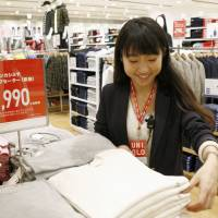 A worker seen at a Uniqlo store in Tokyo. Starting in October, full-time employees at Fast Retailing Co.'s stores can choose to work four days a week. | KYODO