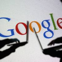 People are silhouetted as they work with laptops in front of a screen onto which the Google logo is projected. Google Inc. is changing its operating structure by setting up a new company called Alphabet Inc., which will include the search business and a number of other units. | REUTERS