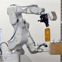 A prototype robot with two arms, developed by Hitachi Ltd. for distribution warehouses, demonstrates its capabilities for the media at a warehouse in Noda, Chiba Prefecture, on Tuesday. | AFP-JIJI