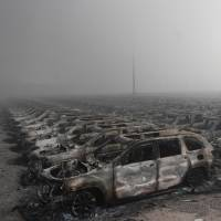 Burned cars are seen in a shipping yard at a chemical warehouse in Tianjin, China, after a series of explosions hit the area on Thursday. Japanese companies operating there have reported only minor damage to their facilities.   AFP-JIJI