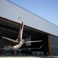 A Mitsubishi Regional Jet passenger aircraft, developed by Mitsubishi Aircraft Corp., stands in a hangar following a rollout ceremony at Mitsubishi Heavy Industries Ltd.'s Nagoya Aerospace Systems Works Komaki South Plant in Toyoyama, Aichi Prefecture, in October 2014. | BLOOMBERG