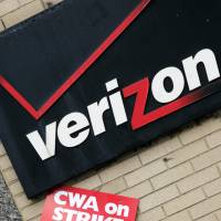A union strike sign hangs in 2011 below Verizon's corporate logo in front of a facility in New York. Verizon workers in nine states could walk off the job again soon  if union negotiators don't reach an agreement over benefits with the wireless carrier. A contract covering 39,000 Verizon workers represented by two unions expired Saturday. | AP