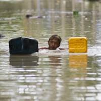 A flood-affected resident swims through floodwaters in Kalay, upper Myanmar's Sagaing region on Monday.  | AFP-JIJI