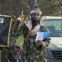 A file picture of a screengrab taken on Oct. 2, 2014, from a video released by the Nigerian Islamist group Boko Haram and obtained by AFP shows Boko Haram leader Abubakar Shekau gesturing as he delivers a speech. The leader of Nigeria's Boko Haram denied he had been killed or ousted as chief of the jihadist group in an audio recording released Saturday attributed to him by security experts. Boko Haram is believed to have been behind an attack last week in Nigeria that left 151 people dead, many of whom drowned. | BOKO HARAM / HO / AFP-JIJI