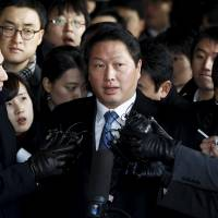 SK Group Chairman Chey Tae-won (center) answers reporters' questions at the Seoul Prosecutors' Office on Dec. 19, 2011.   REUTERS