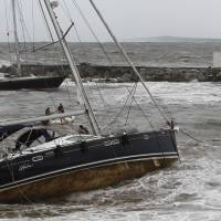 A sloop was blown to the shore by towering waves pounding against the seacoast of Vina del Mar, Chile, on Saturday. | AFP-JIJI
