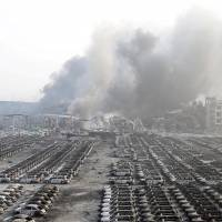 Damaged cars are seen as smoke rises from the debris after the explosions at the Binhai new district in Tianjin, China, on Aug. 13, 2015. Two massive explosions caused by flammable goods ripped through an industrial area in the northeast Chinese port city of Tianjin late on Wednesday, killing 17 people and injuring as many as 400, official Chinese media reported. | REUTERS