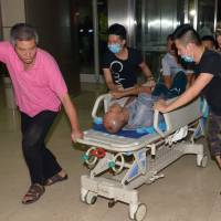 An injured person is brought into a hospital following explosions in China's Tianjin municipality on Thursday. | AP