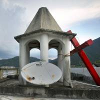 Lay leader Tu Shouzhe stands on the roof of his Protestant church hours after Chinese government workers came and cut down the building's cross (right), in Muyang Village in eastern China's Zhejiang province on July 29. | AP
