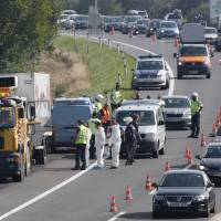 Police prepare to tow a refrigerated truck on the highway near Neusiedl am See, Austria, Thursday. The bodies of between 20 and 50 migrants have been found in the truck.   AFP-JIJI