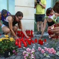 People light candles in front of the police station in Eisenstadt, Austria, Thursday. Austrian police on Thursday discovered the badly decomposing bodies of at least 20 — and possibly up to 50 — migrants stacked in a truck parked on the shoulder of the main highway from Budapest to Vienna near Eisenstadt.   AP