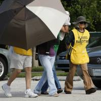 Women are concealed from view by Planned Parenthood volunteers in 2009 as they enter the Planned Parenthood of Collier County in Naples, Florida. Planned Parenthood in Florida asked a judge Monday for an emergency ruling to allow them to continue performing abortions at 12 and 13 weeks after a discrepancy with the state about what constitutes first and second-trimester abortions. A poll released Wednesday found most Americans back federal funds for the nonprofit group. | DAVID ALBERS/NAPLES DAILY NEWS VIA AP, FILE