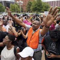Protesters pray at the federal courthouse in downtown St. Louis on Monday. Authorities declared a state of emergency in Ferguson, Missouri, after gunfire erupted on the anniversary of a high-profile police shooting and prosecutors on Monday charged an 18-year-old man with assault on officers. The man, Tyrone Harris, was critically wounded in an exchange of gunfire with police on Sunday night as people marked the shooting death one year ago of unarmed black man Michael Brown by a white officer in Ferguson, a suburb of St. Louis. | REUTERS