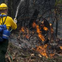 A firefighter from the Washington National Guard fights the First Creek Fire in Chelan, Washington, Tuesday. The U.S. Army mobilized soldiers on Monday to reinforce civilian fire fighters stretched thin by dozens of major wildfires roaring largely unchecked across the West, with more than 100 homes reduced to ruins in several states. | REUTERS