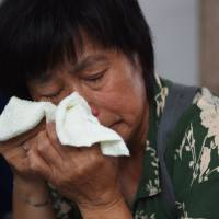 A relative of a passenger on missing Malaysia Airlines MH370 wipes away tears while waiting outside the Malaysia Airlines office in Beijing on Aug. 6, 2015.   AFP-JIJI
